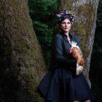 Tier Fotoshootings mit einer Frau die ein Huhn am Arm hält an einem Baum gelehnt mit einem Kranz von misslillyshats