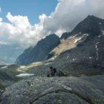 Tierfotograf Tierlicht mit seinem Whippet in den Bergen beim wandern mit Rucksack und Wolken